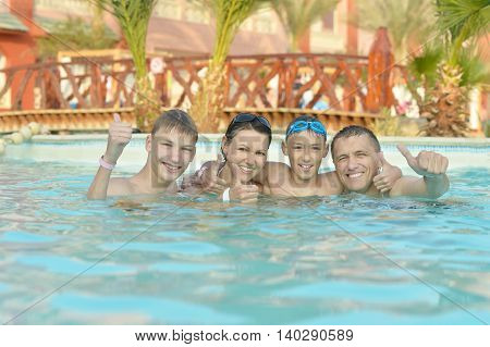 Happy family having fun in pool with thumbs up
