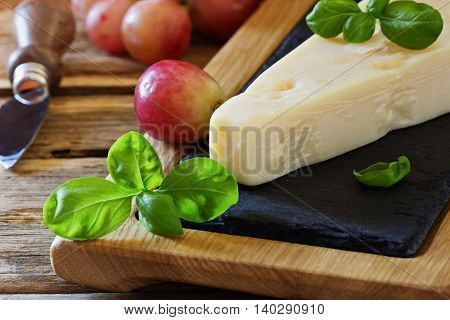Fresh parmesan cheese and ripe grapes on a table. Health and diet food. Selective focus
