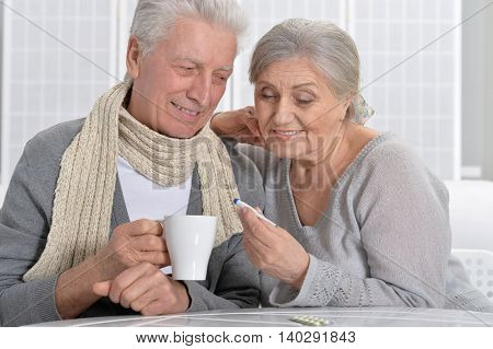 Portrait of a ill senior couple with thermometer