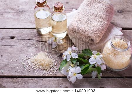 Sea salt towels aroma oil in bottles and flowers on vintage wooden background. Selective focus.Copy space.