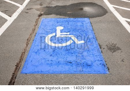 Painted handicapped symbol on old and decaying asphalt.