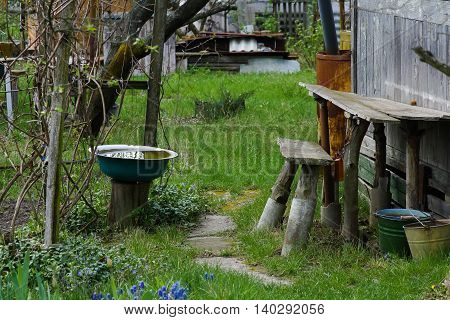 rural yard in early spring completely empty of people there the water from the rain is collected in a basin metal