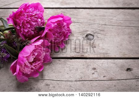 Bunch of pink peonies flowers on aged wooden background. Flat lay. Selective focus. Place for text.