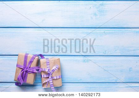 Two festive gift boxes with presents on blue wooden background. Selective focus. Place for text.