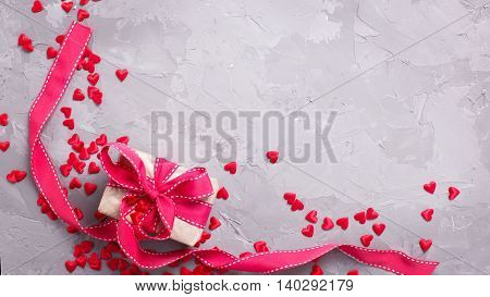 Festive background. Gift box with red ribbon and many little decorative red hearts on textured grey concrete. Flat lay with copy space.