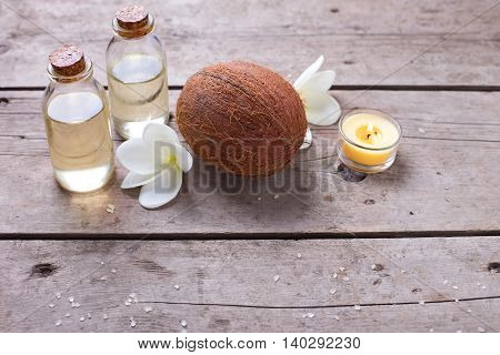 Organic spa products. Bottles with coconut oil on wooden background. Selective focus.