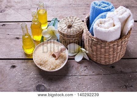 Spa or wellness setting in blue yellow and white colors. Bottles wih essential aroma oil towels sea salt on aged wooden background. Selective focus.