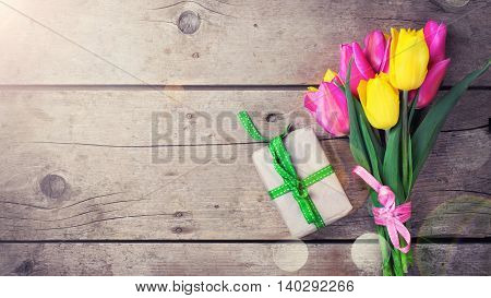 Background with bright yellow and pink spring tulips flowers and box with present. Selective focus. Place for text. Toned image.