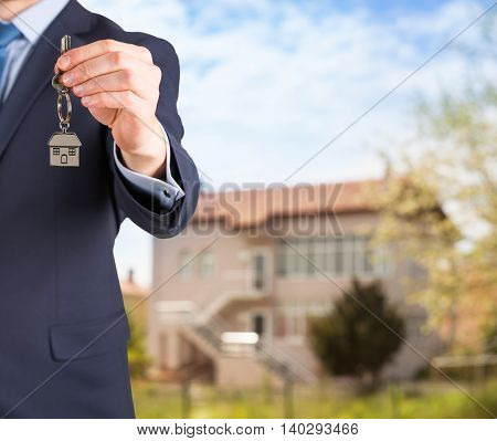 Estate agent giving house keys on defocused background Working Conceptual Business Concept