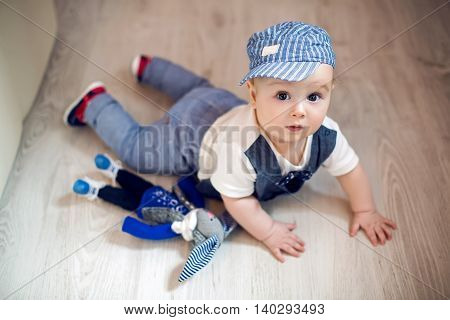 boy kid blonde in a cap and pants lying on the floor next to a toy rabbit