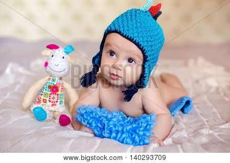 baby is lying on her belly on a big white bed in a big blue hat, and sitting next to a toy goat