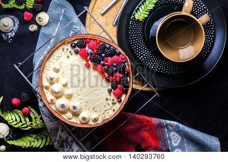 Cake with white chocolate mousse, lime confit, fruits and berries on top as decoration. The process of preparing a tea party with homemade fresh cake. Top view.