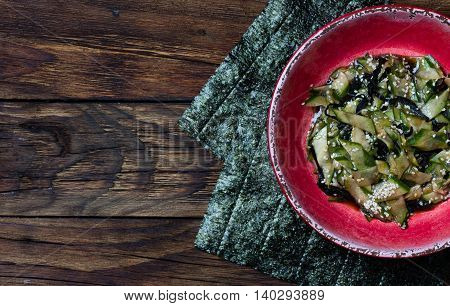 Asian food. Asian salad with seaweed nori, cucumber, white sesame seeds and soya in red bowl on wooden rustic background. Top view