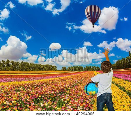 The boy with the globe in hands standing on a field of buttercups and look at flying balloons. Israel spring