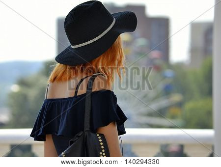 summer travel red-haired girl in a black hat and a black tank top with backpack Rear view