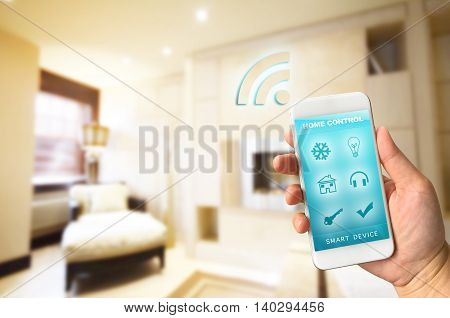 Woman hand holding smartphone against blur of living room background smart home control concept