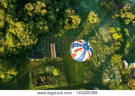 striped balloon flies over a field and houses view from above.