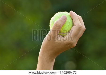 hand holding tennis ball on green blurred background