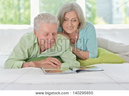 happy Senior couple with magazine at home