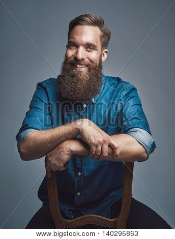Laughing Man With Arms On Back Of Chair Over Gray