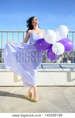 Girl brunette in blue dress posing with white and purple air balloons on roof