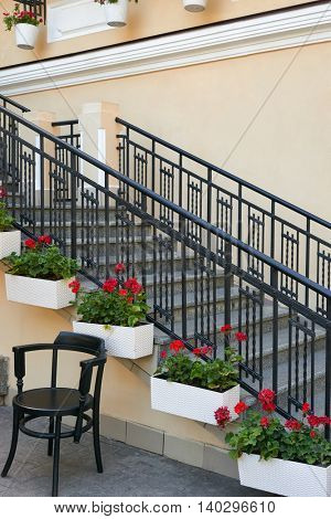stairs to street cafe in city, tables and chairs, ornate with flowers, summer season, no people