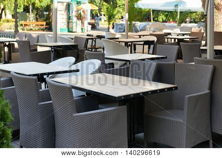 street cafe interior in city without people, tables and chairs, summer season