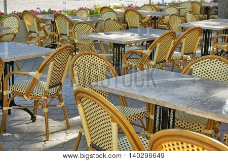 empty street cafe interior in city, tables and chairs, ornate with flowers, summer season, without people