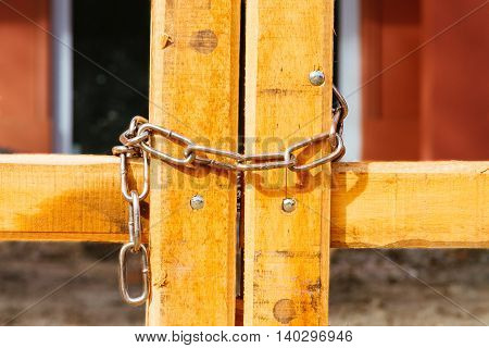 Wooden field gate closed detail with chain