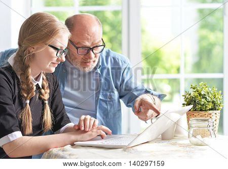 portrait of happy grandfather and  granddaughter using laptop