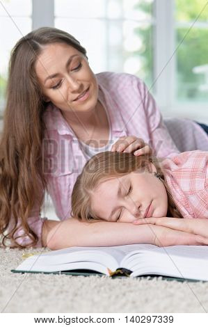 portrait of girl sleeping on book while mother caring for her