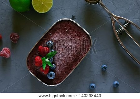 Raspberry and blueberry homemade ice cream in a metal bowl, decorated with raspberries, blueberries, mint and Ice-cream scoop, raspberries, blueberries and lime on a gray background