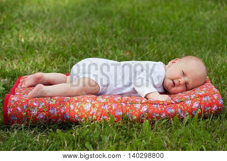 Newborn baby laying on a red blanket on green grass and smiling