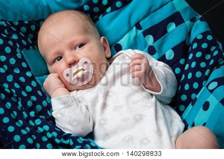 Newborn baby with a nipple on a blue blanket
