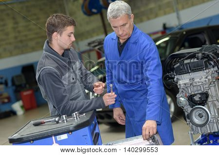 mechanic helping apprentice to fix engine