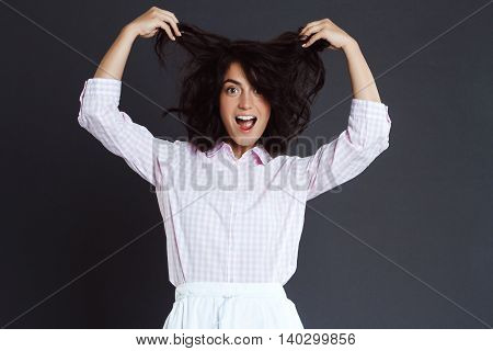 Happy funny woman posing over grey background