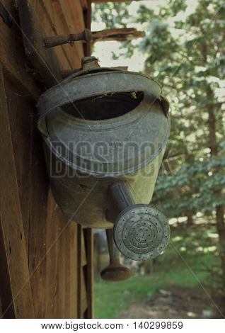 Metal watering cans hanging outside on hooks