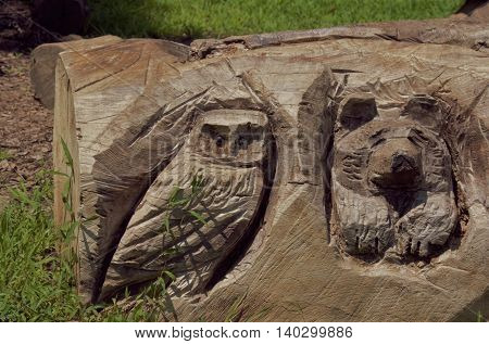 Owl and bear figures carved into a large downed tree