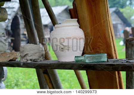 Damaged clay pot and glass botle on wooden shelf.