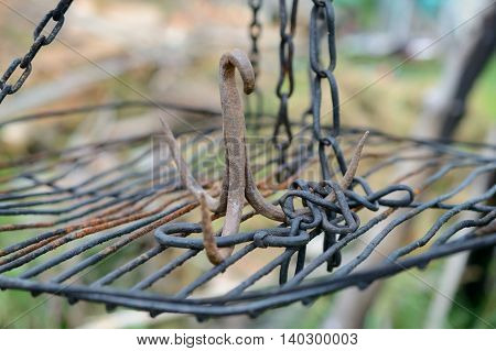 Rusty iron triple hook on grate hanging on chains. Shallow depth of field.