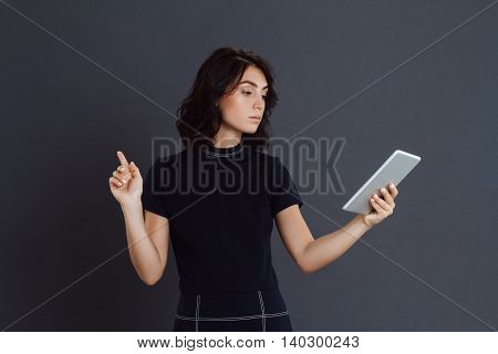 Young woman posing over grey background and holding tablet in hands