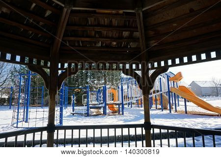 JOLIET, ILLINOIS / UNITED STATES - NOVEMBER 24, 2015: A view of a playground from inside a gazebo in Joliet, after a November snow storm.