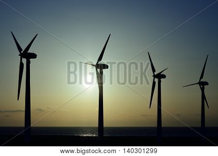 Wind turbines at dawn with intense sun background