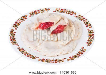 Ukrainian dumplings with strawberries on plate on white background isolated