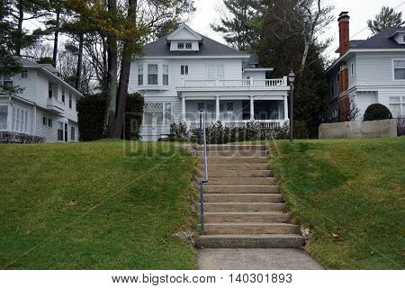 WEQUENTONSING, MICHIGAN / UNITED STATES - DECEMBER 22, 2015: A concrete stairway leads to a white home, on Beach Drive in Wequetonsing.