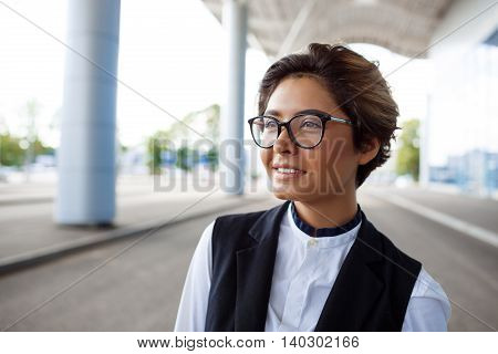 Young successful businesswoman in glasses smiling, standing near business centre.