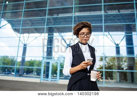 Young successful businesswoman in glasses looking at phone, holding coffee standing near business centre.