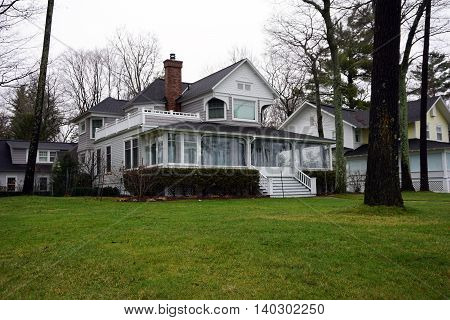 WEQUENTONSING, MICHIGAN / UNITED STATES - DECEMBER 22, 2015: The front porch of a white home, on Beach Drive in Wequetonsing, is protected with plastic sheeting from the winter weather.