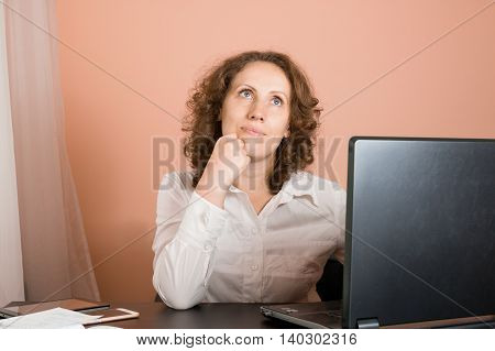 Dreaming Smiling Woman Sitting At A Laptop