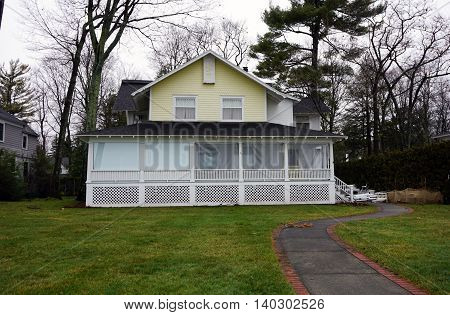 WEQUENTONSING, MICHIGAN / UNITED STATES - DECEMBER 22, 2015: The front porch of a yellow home, on Beach Drive in Wequetonsing, is protected with plastic sheeting from the winter weather.
